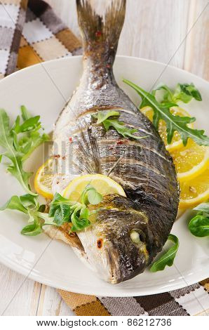 Fried Sea Bream Fish On Plate With Fresh Salad And Lemon.