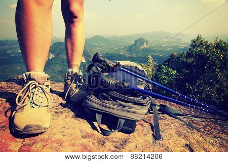 young woman hiker legs climbing at mountain peak rock