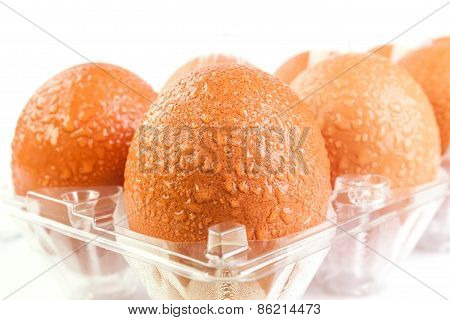 Brown Eggs And Water Drops In Plastic Package After Refrigerator On White Background.