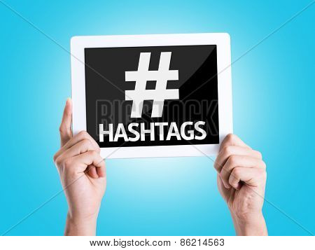 Tablet pc with text Hashtags with blue background