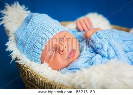 Newborn baby boy portrait in blue knitted hat