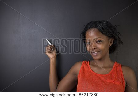 South African Or African American Woman Teacher Or Student Holds Points Chalk On Blackboard