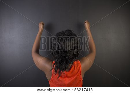 South African Or African American Woman Teacher Or Student Fists Up On Blackboard