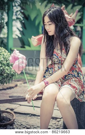 Cute Thai Girl Is Sitting While Holding Pink Candyfloss In Vintage Color