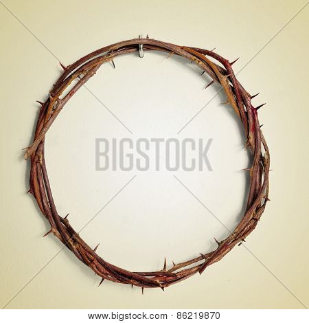 a depiction of the Crown of Thorns of Jesus Christ hanging from a nail on a wall, with a retro effect