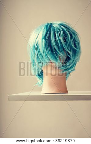 a blue wig in a mannequin head on a white shelf mounted on the wall