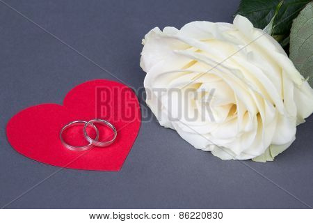White Rose Flower And Wedding Rings On Red Heart Over Grey