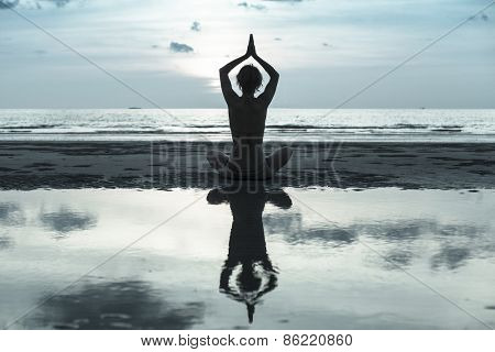 Silhouette young woman practicing yoga on the beach, image in cold colors.