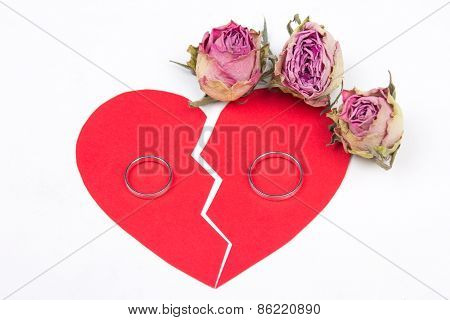 Divorce Concept - Wedding Rings On Red Broken Heart With Dry Flowers Isolated On White
