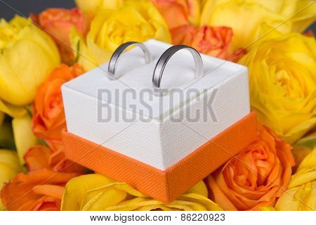Bouquet Of Orange And Yellow Rose Flowers And Wedding Rings In Box