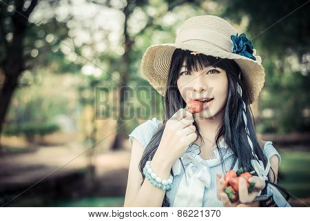 A Cute Asian Thai Girl With Vintage Clothings Is Eating Strawberry She Picked Up In The Forest In Fa