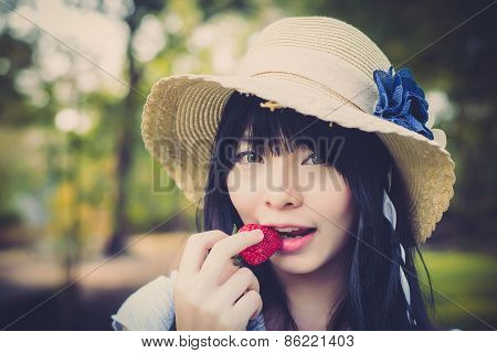 A Cute Asian Thai Girl With Vintage Clothings Is Biting Strawberry She Picked Up In The Forest In Vi