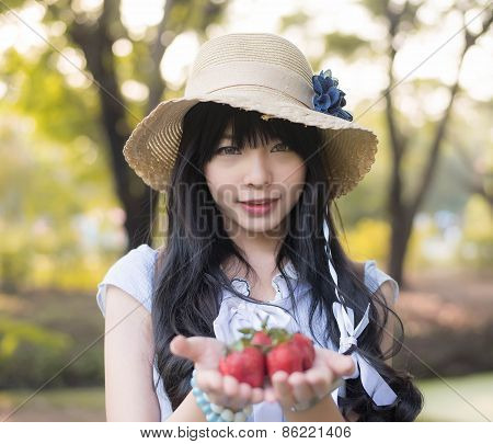 A Cute Asian Thai Girl With Vintage Clothings Is Giving Strawberries