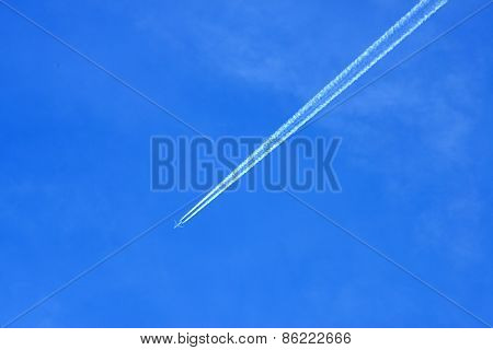 Condensation Trace Left From A Airplane On Blue Sky