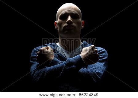 Young hairless man in shadow with arms crossed