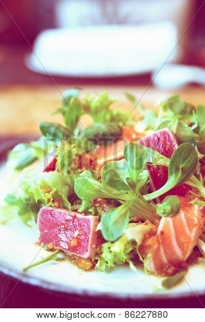 Appetizer with rare fried tuna and salmon , close-up, toned image
