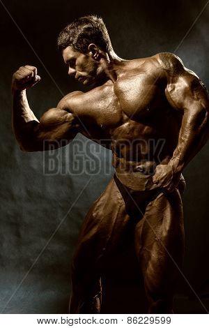 Handsome Muscular Bodybuilder Posing Over Dark Background
