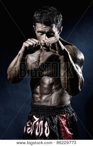 Fighter In A Rack With Fists. Portrait Of A Kick-boxer