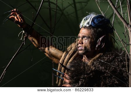 Werewolf With Long Nails And Crooked Teeth Among The Branches Of The Tree