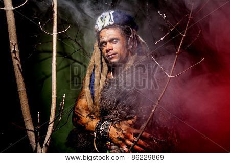 Werewolf With Long Nails And Hair Dreadlocks Among The Branches Of The Tree