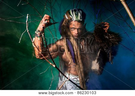 Muscular Man With Dreadlocks And Skin Through The Trees.