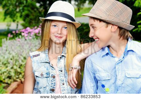 Two cheerful teenagers in the summer park. Friendship.