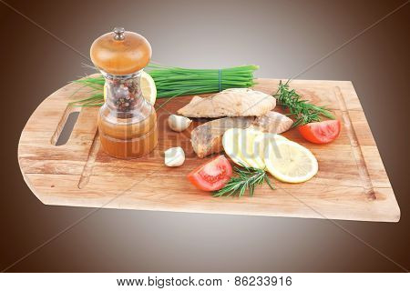 sea food : roasted pink salmon fillet with chinese onion, cherry tomatoes pieces, pepper grinder, rosemary twigs and lemon on wooden board isolated over white background