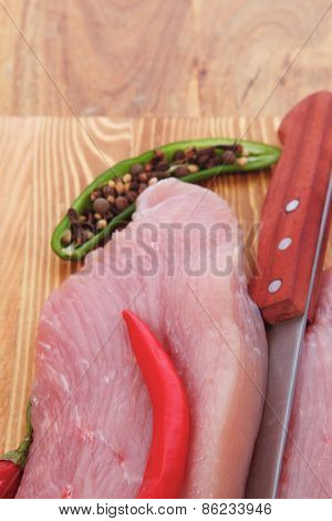 fresh raw turkey steak fillet with red hot chili pepper and green salad on cutting board over wooden table