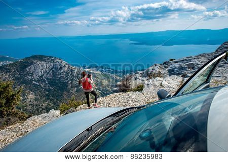 Woman photographer with car on the top of mountain