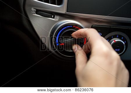 Closeup Shot Of Young Woman Turning Car Air Conditioner Switch