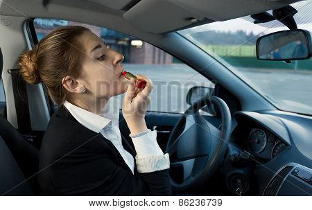 Businesswoman Applying Cosmetics While Driving A Car