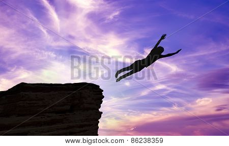 Silhouette Of A Man Jumping Off A Cliff