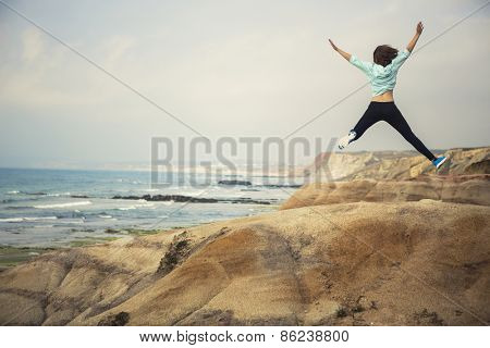 Young woman making a jump with a beautiful beach on the background