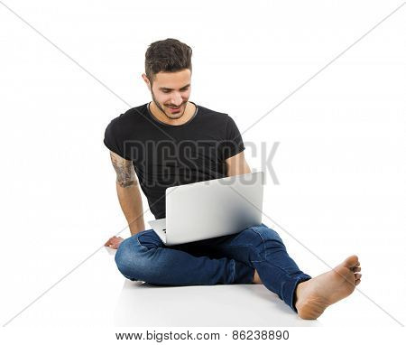 Latin man sitting on the floor and working with a laptop