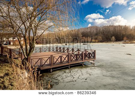 Wooden Pier On Lake Covered By Ice At Sunny Day