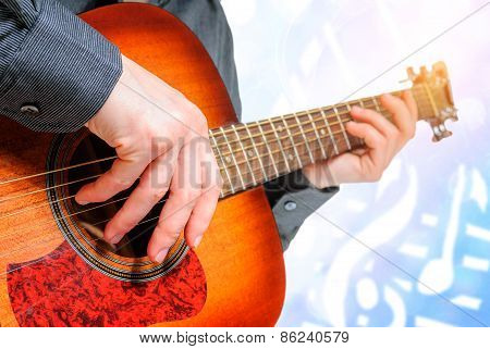 hand to pluck the strings of a guitar