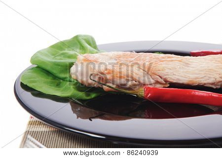 fresh roast turkey meat steak fillet with red hot pepper and green lettuce salad kale on black plate isolated over white background