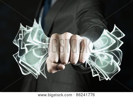 Close up of businessman grasping dollar banknotes in fist