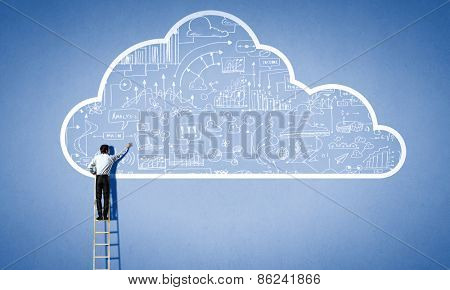 Rear view of businessman standing on ladder and reaching cloud