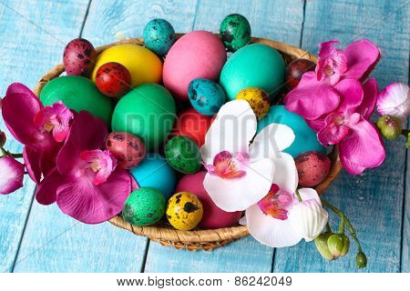 colorful Easter eggs in a basket on a blue table