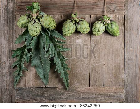 Raw Artichokes On A Aged Table