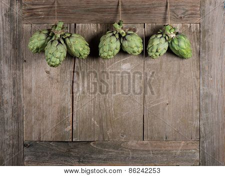 Fresh Artichokes Hanging From Wooden Table