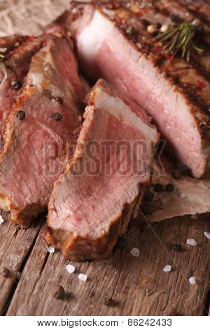 Sliced Grilled Beef Steak On An Old Table.  Vertical Close-up