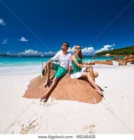 Couple in green sitting on a rock at tropical Seychelles beach