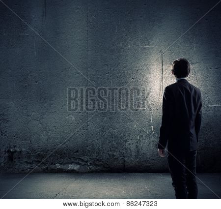 Rear view of businessman looking at blank cement wall