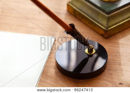 Retro style pen, pen stand and paper or memo on wooden desk.  Focus is on pen base. Shallow depth of field