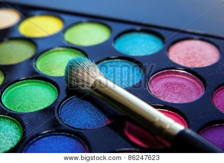 Make-up Brush And Eyeshadow Palette Over Black Close Up.