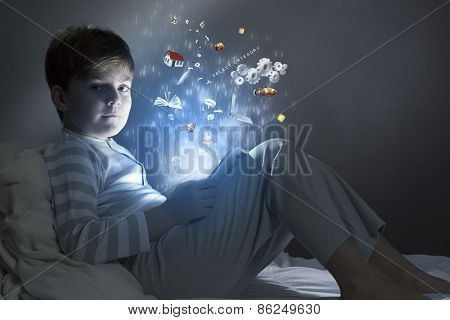 Cute little boy sitting in bed and using tablet pc