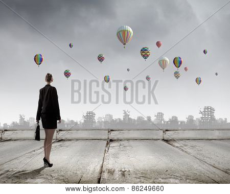 Rear view of businesswoman looking at aerostats flying above city