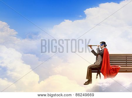 Young man in superhero costume sitting on bench